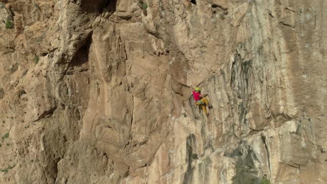 vídeos de stock, filmes e b-roll de aerial follows rock climber as he ascends sandstone rock face - corda de escalada
