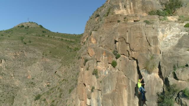 aerial follows rock climber as he ascends sandstone rock face - 登山用具点の映像素材/bロール