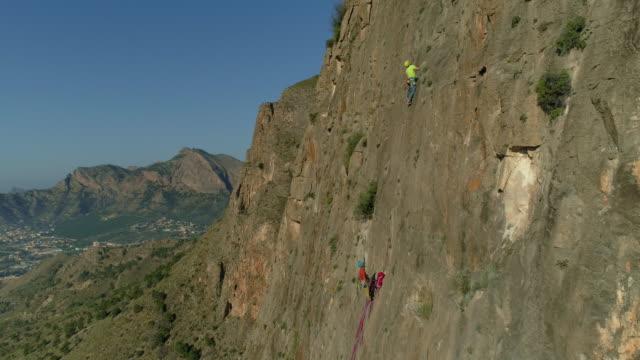 aerial follows rock climbers as he ascends sandstone rock face - 登山用具点の映像素材/bロール