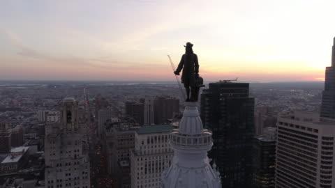 aerial footage circling the william penn statue on top of philadelphia city hall - philadelphia pennsylvania stock videos & royalty-free footage