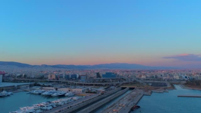 Aerial footage -  Drone - flying over a marina and into a traffic hub in south Athens, Faliro, Greece at sunset
