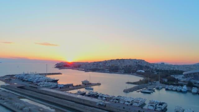 aerial footage -  drone - flying over a marina and into a traffic hub in south athens, faliro, greece at sunset - athens greece stock videos & royalty-free footage