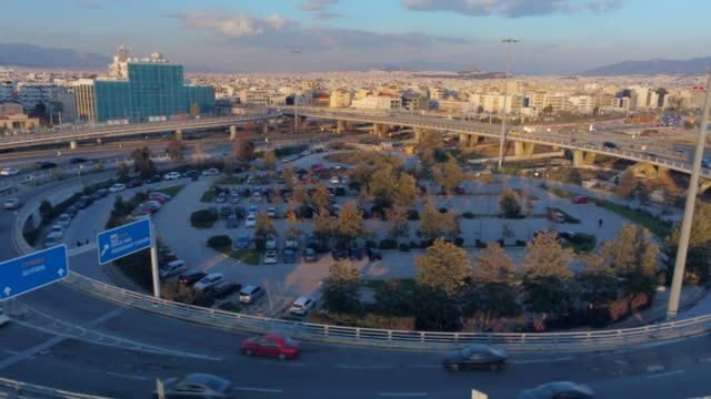 aerial footage -  drone - flying over a marina and into a traffic hub in south athens, faliro, greece at sunset - athens greece video stock e b–roll