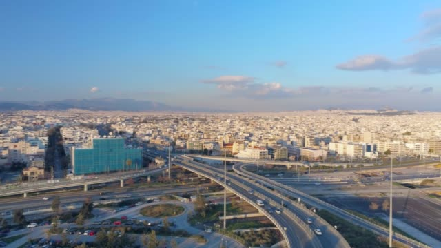 aerial footage -  drone - flying over a traffic hub in south athens, faliro, greece at sunset - athens greece stock videos & royalty-free footage