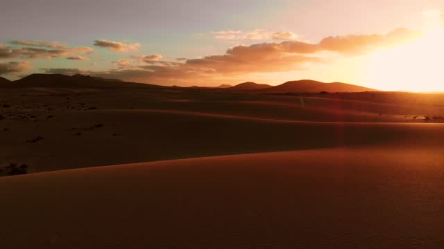 vidéos et rushes de aerial footage flying above sand dunes in desert with dramatic sunset sky in fuerteventura island. spain. - coucher de soleil