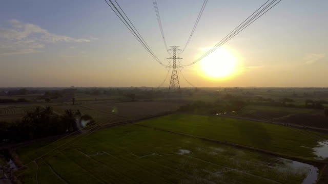 Aerial footage : Flying up the high voltage electricity tower at sunset