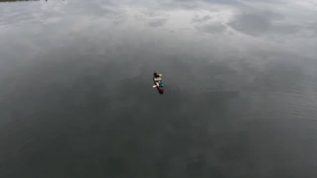 Aerial footage of a canoe being paddled on a glassy calm lake