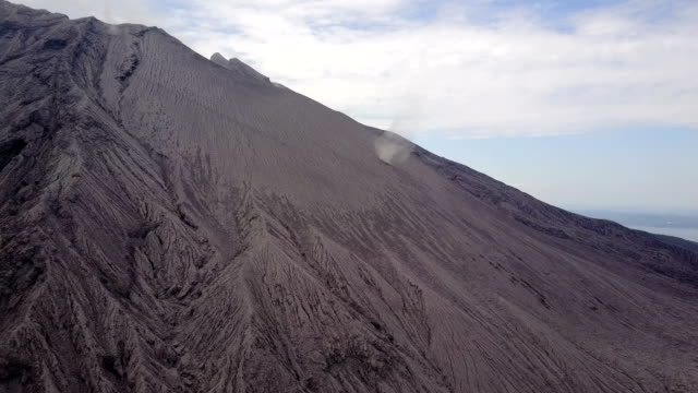 Aerial footage of a dust devil swirling across barren flank of Sakurajima volcano in Japan