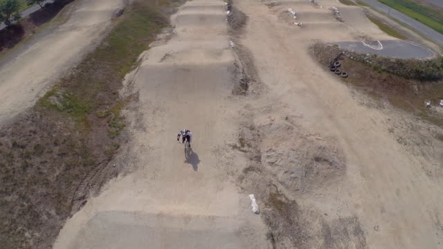 Aerial footage of a female racing a BMX around a track