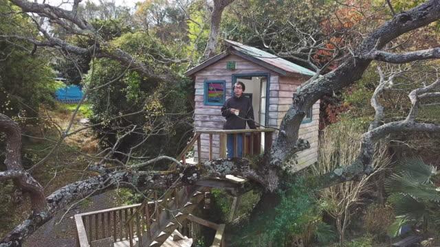 vídeos de stock, filmes e b-roll de imagens aéreas de um homem em uma casa de árvore, bebendo café e apreciando a vista - treehouse