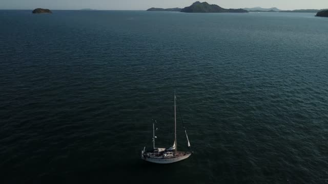 4k aerial footage of a sailboat in phuket with beautiful sunset, thailand. - phuket stock videos & royalty-free footage