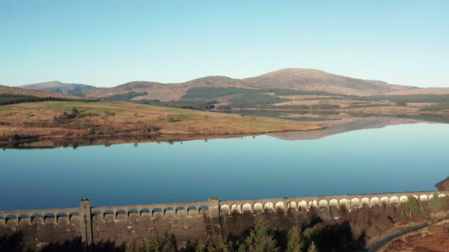 aerial footage of a scottish loch with a hydro electric dam surrounded by hills and an area of forest - 1930 stock videos & royalty-free footage