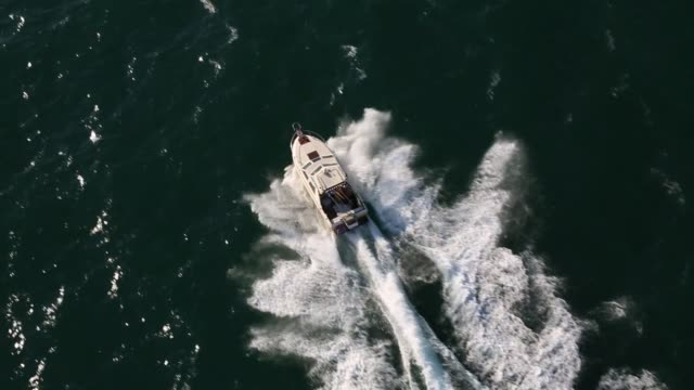 aerial footage of a speed boat cruising through the pacific ocean along santa monica beach in california on july 10th 2015 shots shots follow a... - vagare senza meta video stock e b–roll