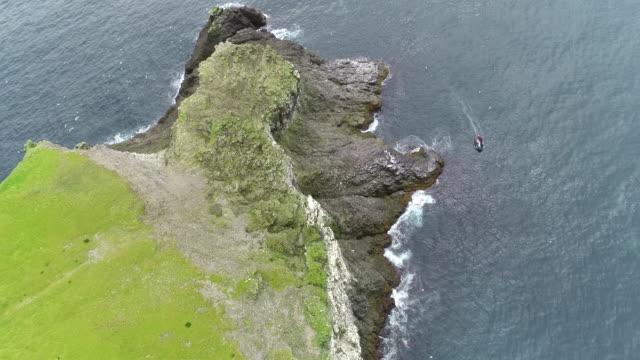aerial footage of a tourist zodiac amongst the seabird cliffs of bear island - スヴァールバル諸島点の映像素材/bロール