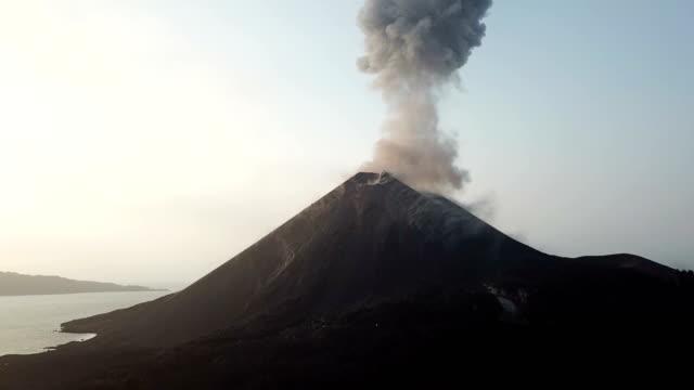 vídeos de stock e filmes b-roll de aerial footage of anak krakatau volcano spewing ash and lava in indonesia - cinza