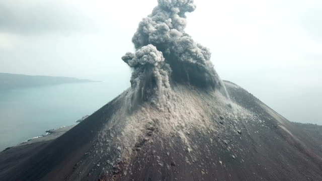 aerial footage of anak krakatau volcano spewing ash and lava in indonesia - eruzione video stock e b–roll