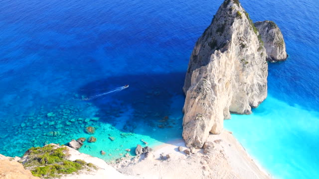 vidéos et rushes de aerial footage of boat sailing between the white cliff with turquoise water in the coastline of zakynthos. 4k. - vertige