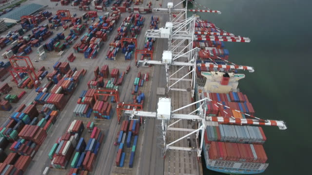 Aerial footage of cargo containers and ship at seaport