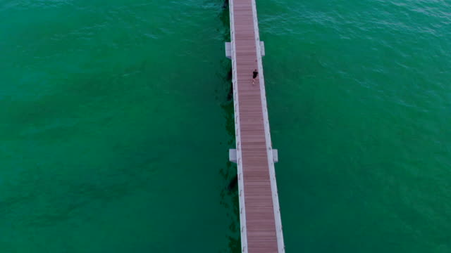 aerial footage of guy running in the morning over infinite pier with the sea. - mittelmeer stock-videos und b-roll-filmmaterial