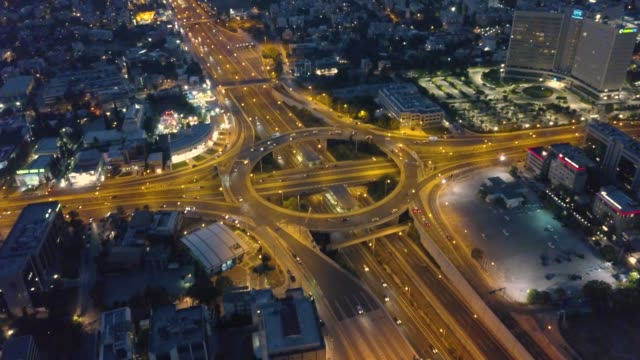 aerial footage of highway intersection at night with cars moving - road junction stock-videos und b-roll-filmmaterial