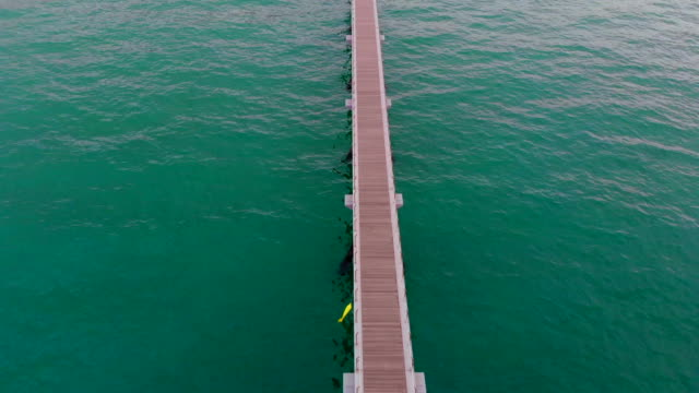 Aerial footage of infinite pier over the sea.
