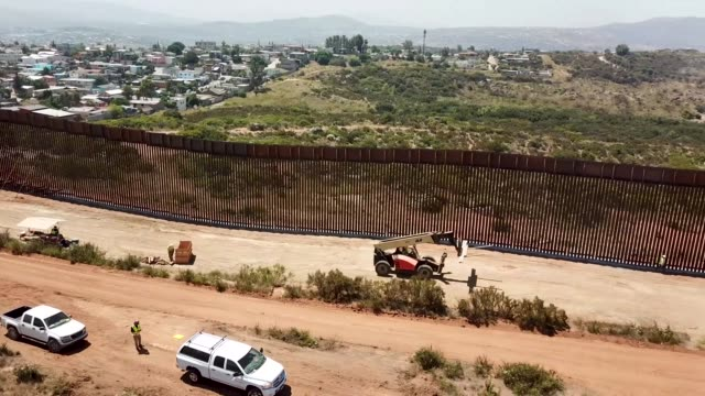 vídeos de stock e filmes b-roll de aerial footage of new installed border wall near tecate port of entry tecate california 19 june 2019 - muro circundante