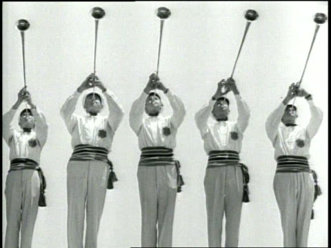 Aerial footage of Olympic Stadium and park / Medium long shots of five trumpeters in white with horns up playing in unison / Brief long shot of...