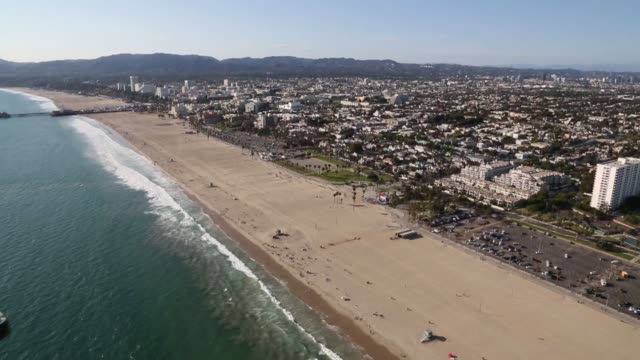 aerial footage of people lounging on the beach along the pacific ocean in santa monica california on july 10th 2015 shots aerials move along the... - adagiarsi video stock e b–roll