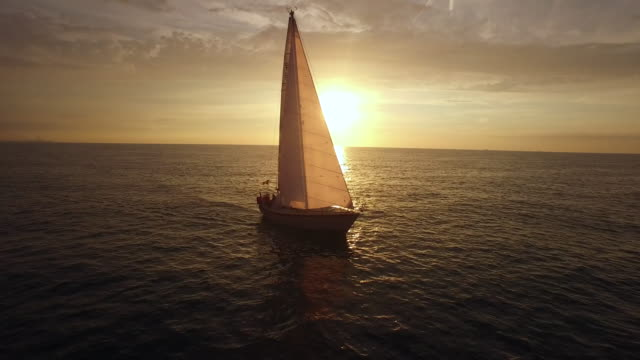 Aerial footage of sailboat during sunset.