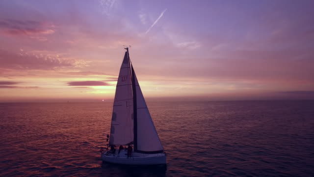 aerial footage of sailboat during sunset. - yachting stock videos & royalty-free footage