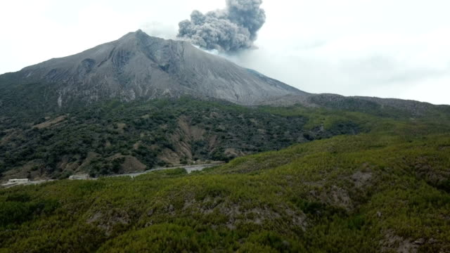 aerial footage of sakurajima volcano erupting large cloud of volcanic ash from summit crater - vulkanausbruch stock-videos und b-roll-filmmaterial