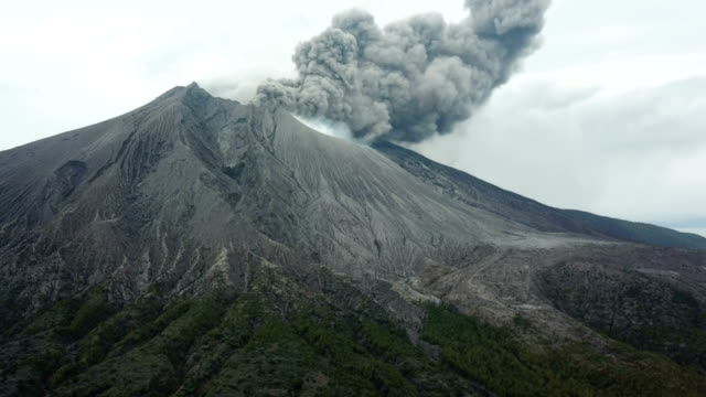 Aerial footage of Sakurajima volcano erupting large cloud of volcanic ash from summit crater