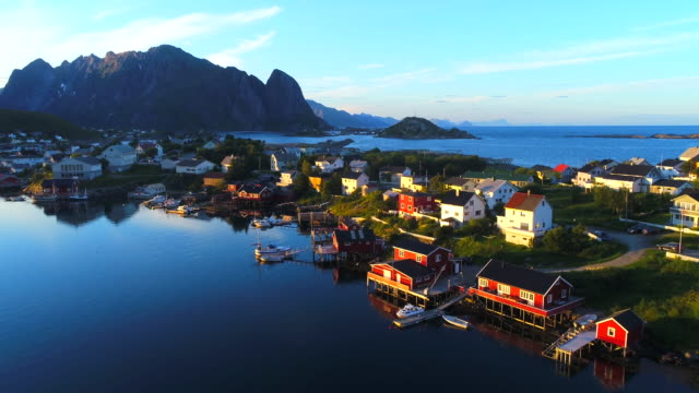 aerial footage of small fishing village of hamnoy on lofoten islands in norway, popular tourist destination with its typical red houses and natural beauty. aerial 4k ultra hd. - fishing village stock videos and b-roll footage