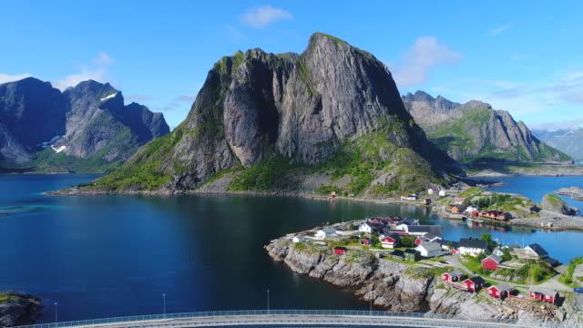 luftaufnahmen von kleinen fischerdorf dorf von hamnoy auf lofoten in norwegen, beliebtes touristenziel mit seiner typischen roten häusern und natürliche schönheit. antenne 4 k ultra hd. - village stock-videos und b-roll-filmmaterial