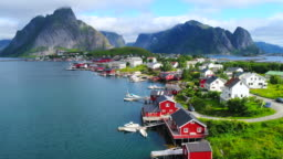 Aerial footage of small fishing village of Hamnoy on Lofoten islands in Norway, popular tourist destination with its typical red houses and natural beauty. Aerial 4k Ultra HD.