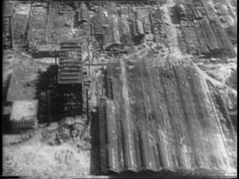 aerial footage of the burnout remains of osaka and yokosuka / a carrier ship lays overturned on its side another destroyed carrier in kure harbor / a... - 1945点の映像素材/bロール