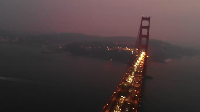 Aerial footage of the Golden Gate bridge at night with cinematic effect.