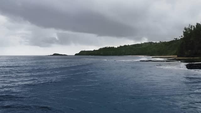 aerial footage of the reef near a tropical shore under gray clouds (kauai, hawaii, usa) - kauai stock videos & royalty-free footage