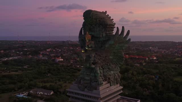 vídeos de stock, filmes e b-roll de aerial footage of the sunset over garuda wisnu kencanal statue in the island of bali in indonesia - ponto turístico internacional