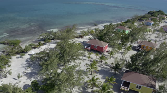 aerial footage of tourist resorts with trees on island by sea during sunny day - coco plum cay, belize - shack stock videos & royalty-free footage