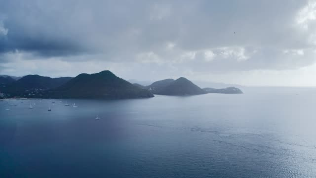 aerial footage of yachts near the mountains on the shore of a calm sea, overcast on the horizon (rodney bay, saint lucia) - 半島点の映像素材/bロール
