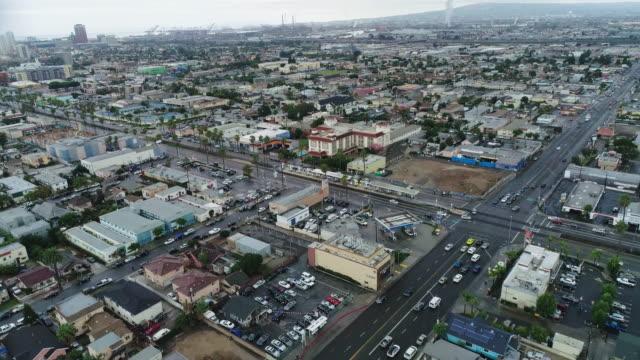 aerial footage over a long beach, california neighborhood and commuter train - long beach california video stock e b–roll