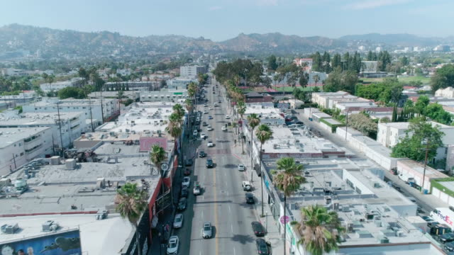 aerial footage over fairfax avenue shopping district in los angeles - local landmark stock videos & royalty-free footage