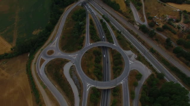 Aerial footage recorded with drone flying over a highway with roundabout and railroad track in the industry place of the Catalonia region. 4K UHD.
