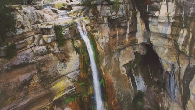 Aerial footage recorded with drone flying over a nice waterfall with hundred meters drop and stunning cliff during the rainy season in the Catalonian mountains. 4K UHD.