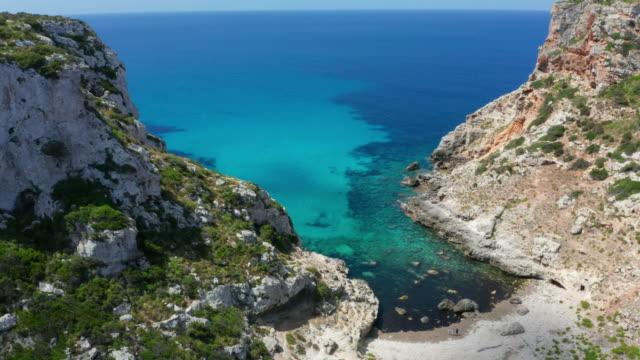 vídeos de stock, filmes e b-roll de imagens aéreas gravadas com drones voando sobre uma costa deslumbrante de menorca com mar azul claro. 4k - baía