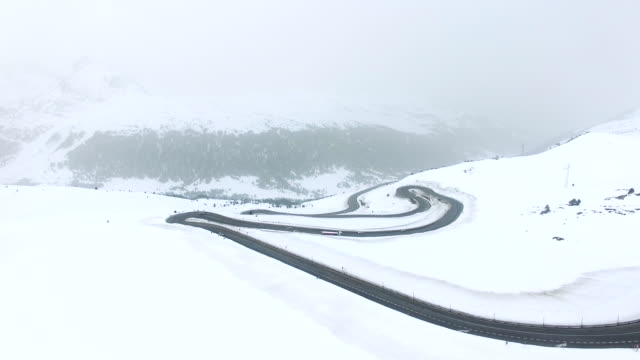 Aerial footage recorded with drone flying over a stunning mountain road with snowy landscape and nice curves with car driving in the Pyrenees mountains landscape. 4K UHD.