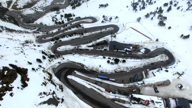 Aerial footage recorded with drone flying over a stunning mountain road with snowy landscape and nice curves with cars driving in the Pyrenees mountains landscape. 4K UHD.