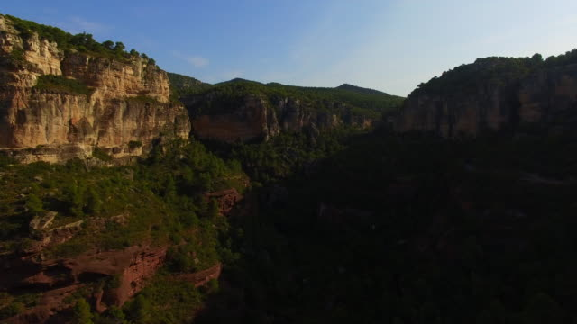 Aerial footage recorded with drone flying over a stunning mountain valley with rock formations with forward motion and stunning landscape, sunny days in the Tarragona mountains. 4K UHD.