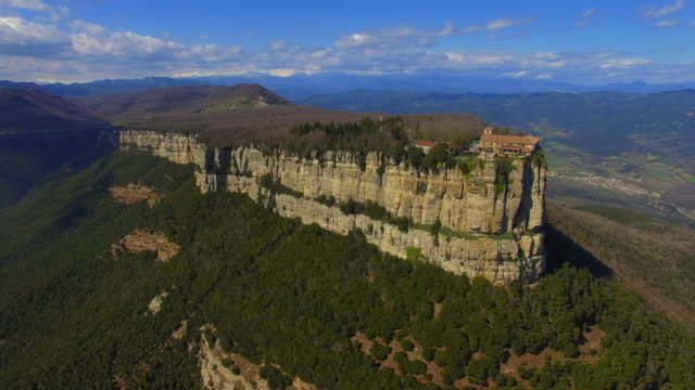 Aerial footage recorded with drone flying over a stunning mountains with big cliff and boat shape in the Catalonia region of Collsacabra mountains with the Pyrenees mountains in the background. 4K UHD.